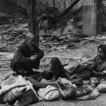 Civilians huddle in the streets of Seoul, South Korea amid rubble and debris, after fierce fighting between UN and North Korean forces, during the Korean War - 1950