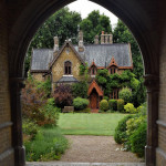 Victorian Gothic cottage beyond the arch of the gatehouse in Holly Village, Highgate, North London, UK