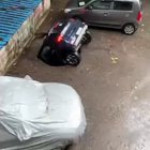 Concrete ground breaks open, sinking a parked car in underground water