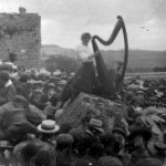A young lady playing a large harp to the crowd in 1910 Ireland
