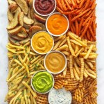 Perfectly aligned fries and sauce with a perfect mix of colours on a board