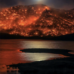 The moon rising over a hill in California, engulfed in a wildfire