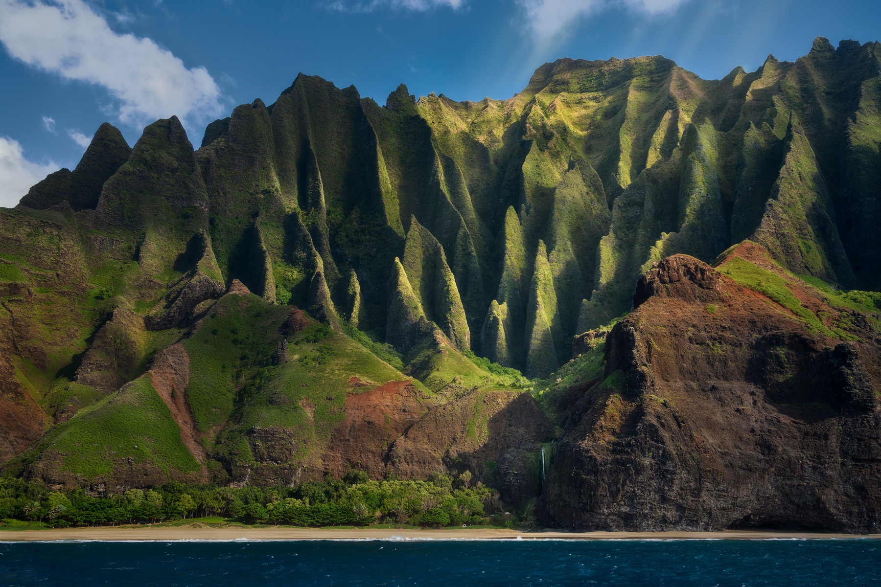 The sun filtering through storm clouds by the Napali coast light