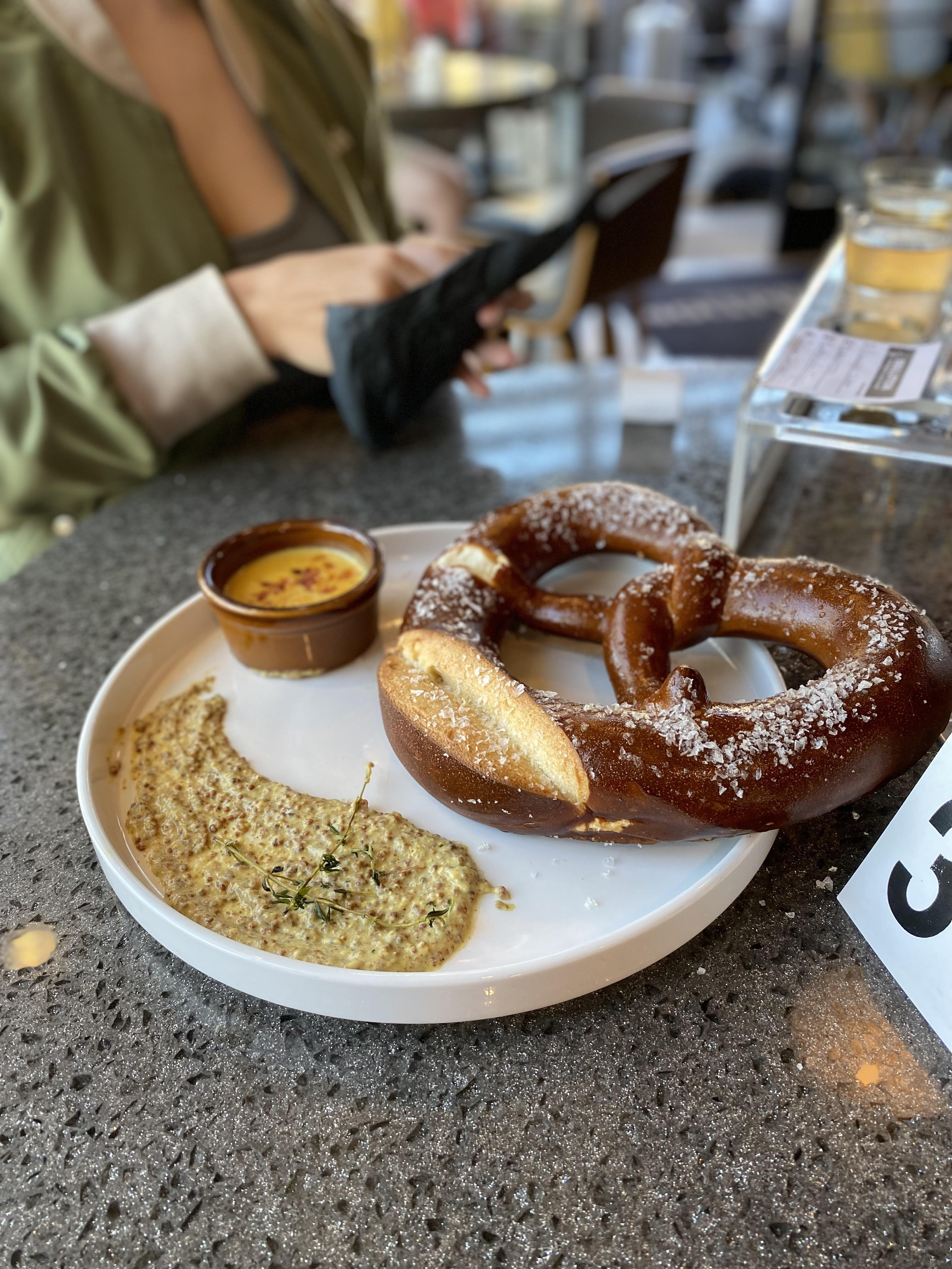 Pretzel with mustard spread and beer cheese dip