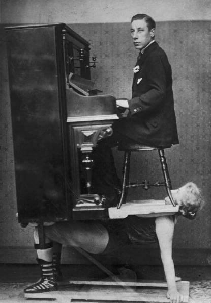 A circus strongwoman balances a piano and pianist on her chest, circa 1920 🎪